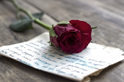 Love letter and rose on wooden background,close up